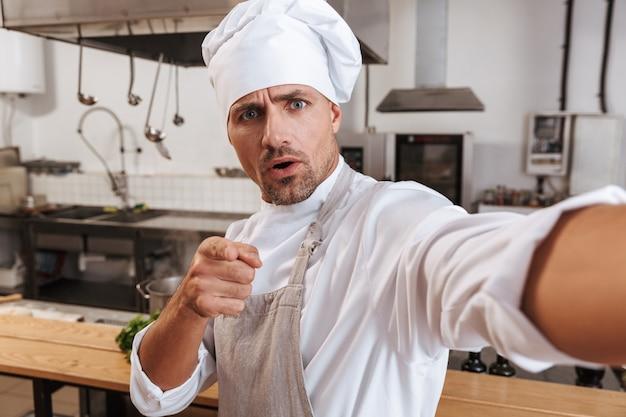 Zdjęcie szczęśliwy wódz mężczyzna w fartuchu, biorąc selfie, stojąc w kuchni w restauracji