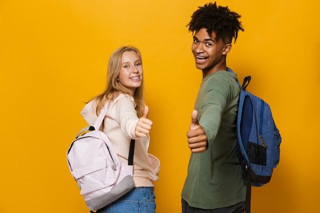 Zdjęcie szczęśliwych studentów, mężczyzny i kobiety w wieku 16-18 lat, noszących plecaki, śmiejących się i pokazujących kciuki w górę, odizolowanych na żółtym tle