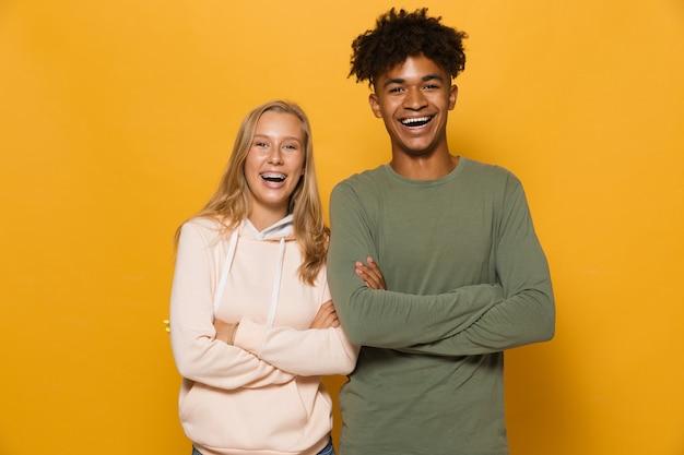 Zdjęcie szczęśliwych studentów mężczyzny i kobiety w wieku 16-18 lat z aparatami ortodontycznymi, śmiejących się z kamery, odizolowane na żółtym tle