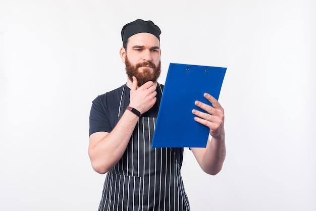 Zdjęcie szefa kuchni mężczyzna patrząc na składniki w notatkach