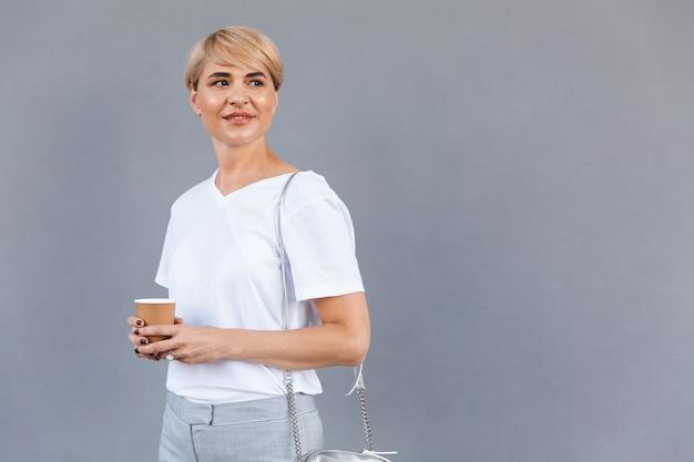 Zdjęcie treści dojrzała kobieta ubrana w białą koszulkę stojącą na białym tle nad szarą ścianą i trzymająca kawę z papierowego kubka