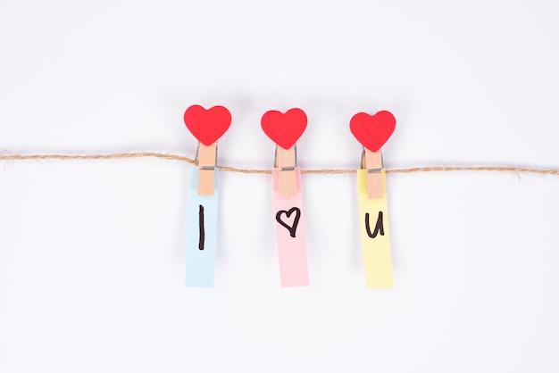 Zdjęcie trzech ładnych spinaczy do bielizny w kształcie serca trzymających kolorowe naklejki z wyznaniem miłości na białym tle