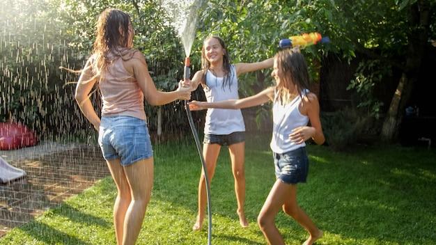 Zdjęcie trzech wesołych nastoletnich dziewcząt tańczących w przydomowym ogrodzie pod wężem ogrodowym