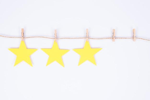Zdjęcie trzech z pięciu gwiazdek w kolorze żółtym, wiszące na wątku dołączonym do małych szpilek ubrania projektowania na białym tle