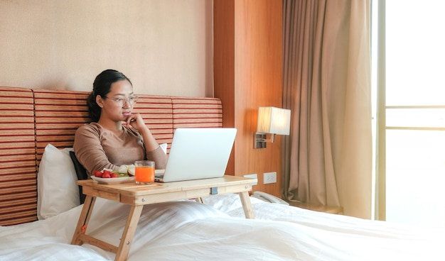Zdjęcie turystów korzystających z laptopa i jedzących owoce na łóżku w luksusowym pokoju hotelowym, koncepcja zdrowej żywności.