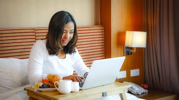 Zdjęcie turystów korzystających z laptopa i jedzących śniadanie na łóżku w luksusowym pokoju hotelowym, koncepcja zdrowej żywności.