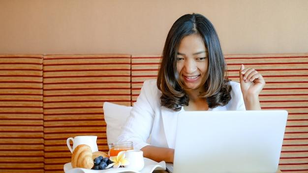 Zdjęcie turystów korzystających z laptopa i jedzących śniadanie na łóżku w luksusowym pokoju hotelowym