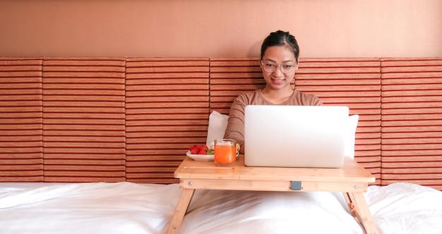 Zdjęcie turystów używa laptopa i jedząc owoce na łóżku w luksusowym pokoju hotelowym koncepcja zdrowej żywności