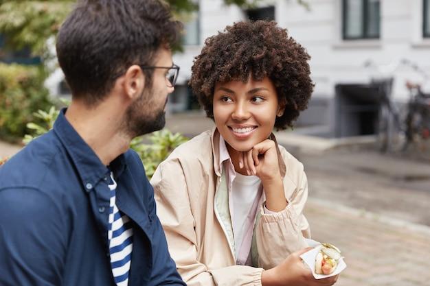 Zdjęcie turysty rasy mieszanej cieszy się ożywioną komunikacją, je fast foodem na ulicy, będąc w dobrym nastroju.