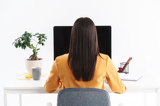 Zdjęcie udanej brunetki 20-latki siedzącej przy stole i pracującej na dużym komputerze w jasnym biurze