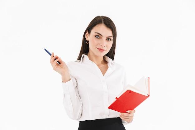 Zdjęcie udanej pracownic bizneswoman ubranej w strój wizytowy, trzymając terminarz podczas pracy w biurze na białym tle nad białą ścianą