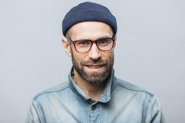 Zdjęcie ujęcia przystojnego nieogolonego mężczyzny o zadowolonym wyrazie twarzy, cieszącego się z sukcesu w pracy