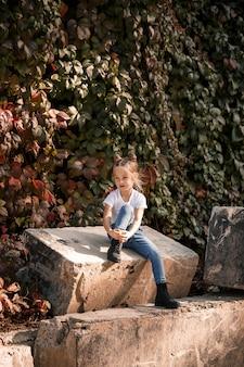 Zdjęcie uliczne małej pięknej dziewczyny w dżinsach i białej koszulce na tle betonowych płyt i jesiennych liści