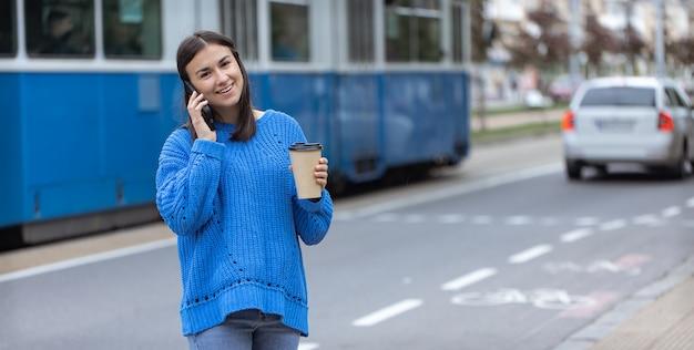 Zdjęcie uliczne młodej kobiety z telefonem w dłoni i kawą na wynos.