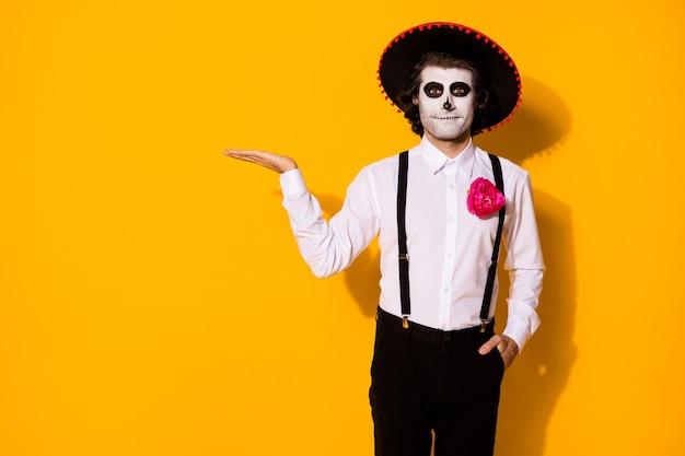 Zdjęcie upiornego duchowego faceta trzymaj pustą przestrzeń proponuj ciekawy rzadki festiwal przedmiot ręka kieszeń nosić biała koszula śmierć kostium cukier czaszka szelki na białym tle żółty kolor tło