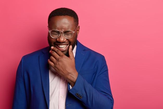 Zdjęcie uradowanego afro amerykanina śmieje się z zabawnej historii, nie może przestać chichotać, ma białe zęby, gęstą brodę, nosi formalny garnitur, zez