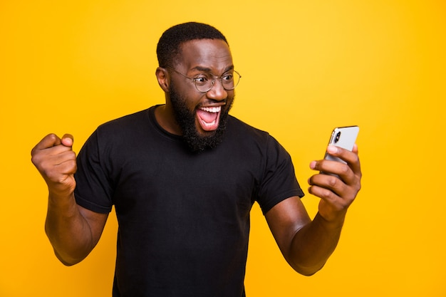 Zdjęcie uradowanego szalonego, niezobowiązującego brązowowłosego brodatego mężczyzny w okularach t-shirt radujących się ze zwycięskiego wydarzenia wyrażającego emocje na twarzy odizolowany żywy kolor żółta ściana