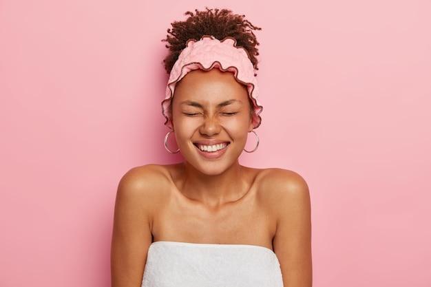 Zdjęcie uradowanej ciemnoskórej kobiety owiniętej w biały ręcznik kąpielowy, nosi różową opaskę prysznicową, przygotowuje się do sauny, ma zdrową, zadbaną ciemną skórę, kręcone czesane włosy, wyraża dobre uczucia