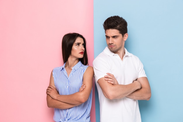 Zdjęcie urażonego mężczyzny i kobiety w zwykłych ubraniach stojących z rękoma w kłótni, na białym tle nad kolorową ścianą