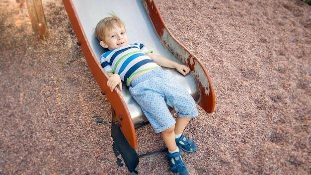 Zdjęcie uroczego 3-letniego chłopca wspinającego się i jeżdżącego na dużej zjeżdżalni na placu zabaw w parku