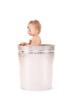 Zdjęcie uroczego dziecka w koszu na śmieci