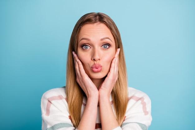 Zdjęcie uroczej, bardzo uroczej miłej dziewczyny całującej cię, dotykającej jej policzków z wydymanymi ustami na białym tle niebieskiej pastelowej ścianie