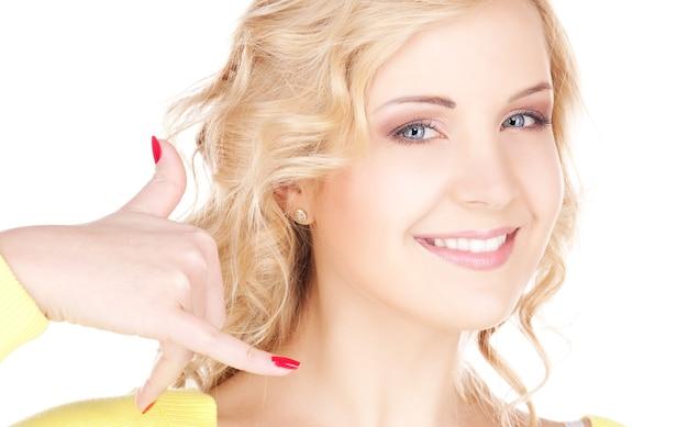 """Zdjęcie uroczej blondynki wykonującej gest """"zadzwoń do mnie"""""""