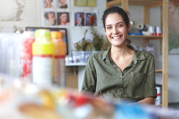 Zdjęcie uroczej, charyzmatycznej młodej artystki w koszuli khaki, szeroko uśmiechającej się, szczęśliwej ze swojej pracy i procesu tworzenia, siedzącej w warsztacie, otoczonej akcesoriami do malowania