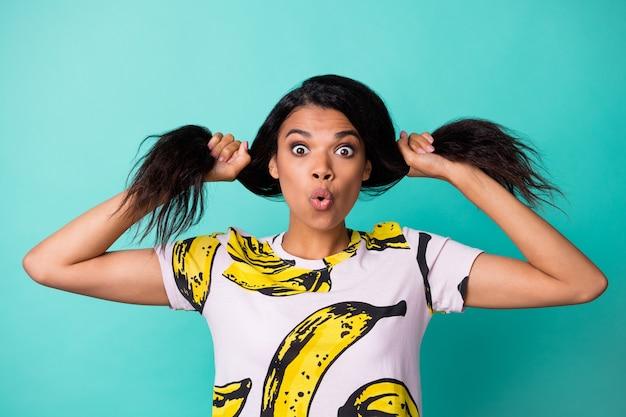 Zdjęcie uroczej czarnej młodej dziewczyny grać faliste ogony w szoku wygląd aparatu nosić banana t-shirt z nadrukiem na białym tle turkusowy kolor tła
