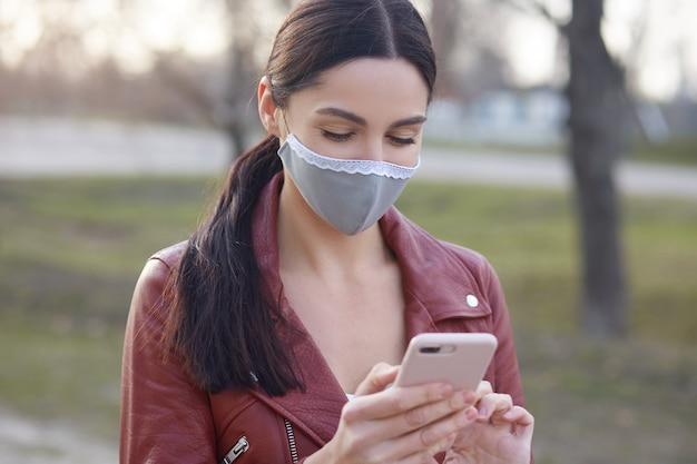 Zdjęcie uroczej dziewczyny o przyjemnym wyglądzie, stojącej na zewnątrz ze smartfonem w rękach, damy czytającej wiadomości o rozprzestrzenianiu się niebezpiecznego wirusa korony