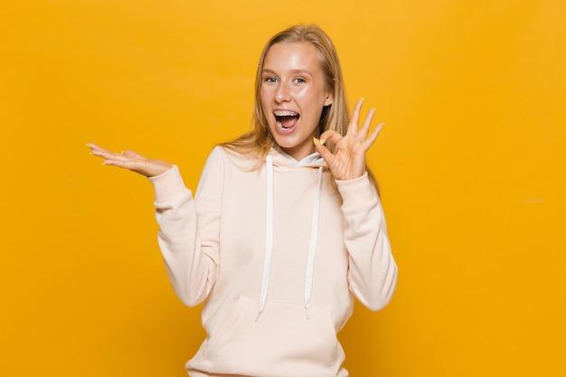 Zdjęcie uroczej dziewczyny w wieku 16-18 lat z aparatami ortodontycznymi, trzymającej copyspace na dłoni, odizolowanej na żółtym tle