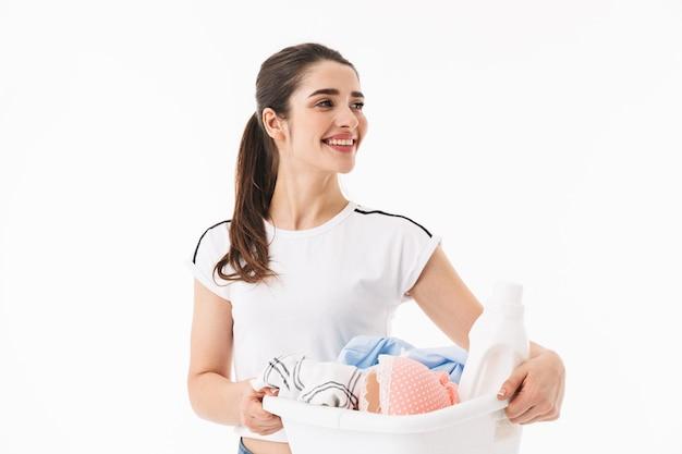 Zdjęcie uroczej kobiety gospodyni domowej w wieku 20 lat ubranej w codzienne ubrania niosącej kosz na pranie z brudnymi, czystymi ubraniami na białym tle nad białą ścianą