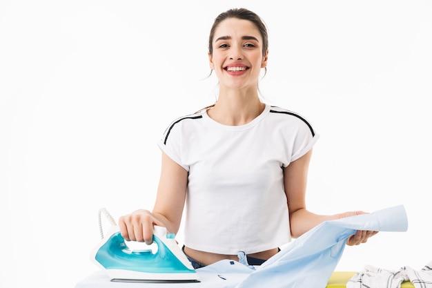Zdjęcie uroczej kobiety gospodyni domowej w wieku 20 lat, ubranej w odzież codzienną, prasowanie czystych ubrań na desce na białym tle nad białą ścianą