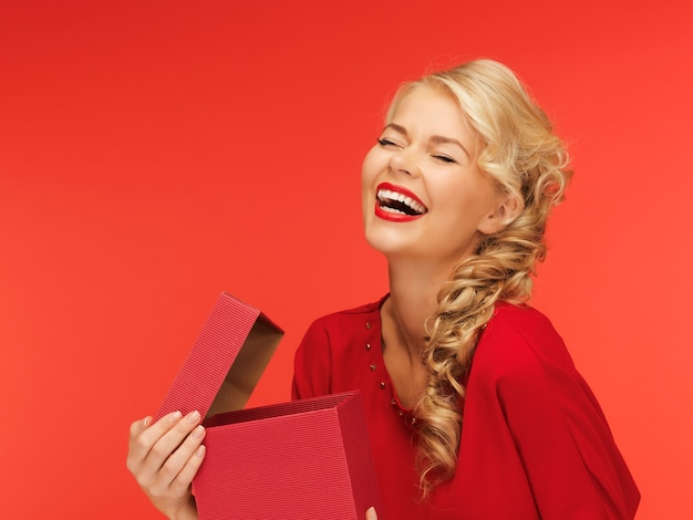 Zdjęcie uroczej kobiety w czerwonej sukience z otwartym pudełkiem na prezent
