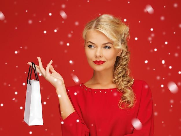 Zdjęcie uroczej kobiety w czerwonej sukience z torbą na zakupy