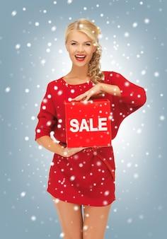 Zdjęcie uroczej kobiety w czerwonej sukience ze znakiem wyprzedaży