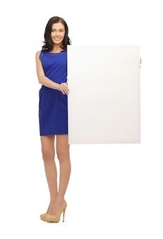 Zdjęcie uroczej kobiety w niebieskiej sukience z pustą tablicą