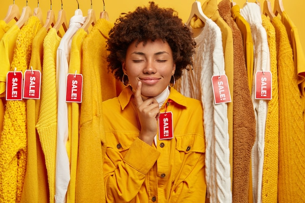 Zdjęcie uroczej kobiety z fryzurą w stylu afro, przymierza nową żółtą kurtkę w garderobie, ma zamknięte oczy, stoi między ubraniami z czerwonymi metkami z napisem wyprzedaż, szuka modnego stroju.