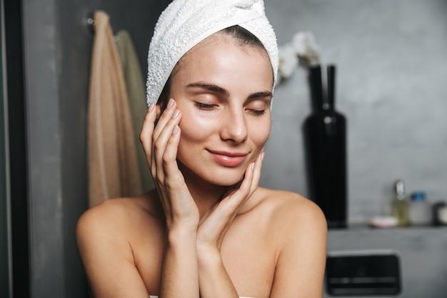 Zdjęcie uroczej kobiety z ręcznikiem na głowie, dotykając jej twarzy po kąpieli