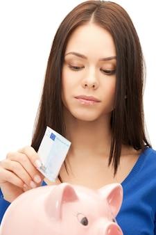 Zdjęcie uroczej kobiety ze skarbonką i pieniędzmi