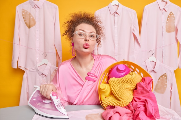 Zdjęcie uroczej, kręconej, zajętej gospodyni domowej trzyma usta złożone w pozie w pobliżu deski do prasowania z koszem na pranie i parowym żelazkiem w przezroczystych okularach, a szlafrok ma romantyczny nastrój