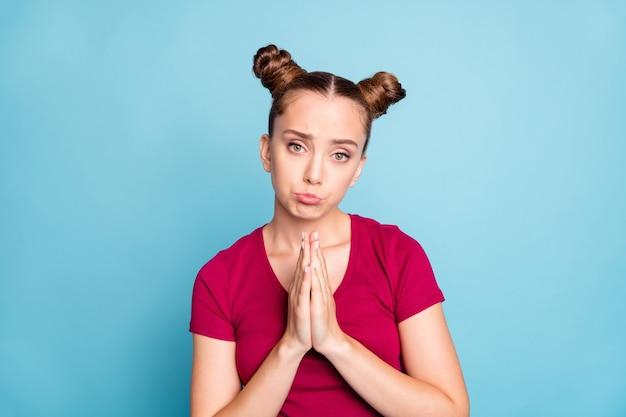 Zdjęcie uroczej, ładnej dziewczyny błagającej cię o wybaczenie ze smutnym wyrazem twarzy rękami złożonymi do modlitwy odizolowanymi na niebieskiej ścianie w pastelowym kolorze