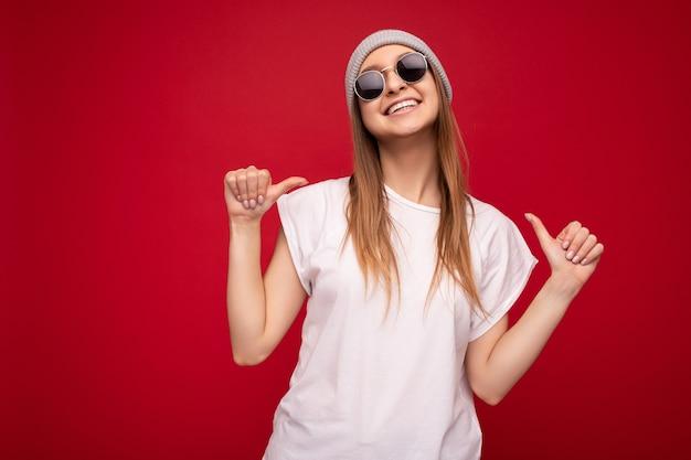 Zdjęcie uroczej, miłej, ujmującej pozytywnej dorosłej kobiety noszącej swobodny strój na białym tle na ścianie w tle