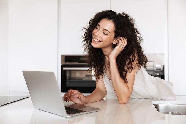 Zdjęcie uroczej młodej kobiety po dwudziestce z kręconymi brązowymi włosami w jedwabnym ubraniu rekreacyjnym, uśmiechającej się z idealnymi zębami i korzystającej ze srebrnego laptopa, opierając się na kuchennym stole