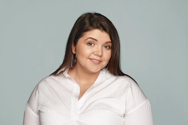 Zdjęcie uroczej młodej kobiety w rozmiarze plus size z czarnymi luźnymi włosami i dużym, zakrzywionym ciałem, uśmiechającą się radośnie, wyrażającą radość i pozytywne emocje, pozowanie na białym tle ubrana w białą formalną koszulę xxl