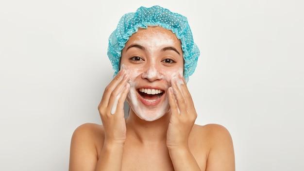 Zdjęcie uroczej modelki o radosnym wyrazie twarzy, myje twarz pieniącym się środkiem myjącym, nosi wodoodporny czepek kąpielowy, pielęgnuje skórę, stoi bez koszuli, wygląda prosto. zabieg na twarz
