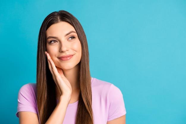 Zdjęcie uroczej myślącej dziewczyny ubranej na co dzień fioletowy strój ramię policzek wygląda pusta przestrzeń na białym tle niebieski kolor tła