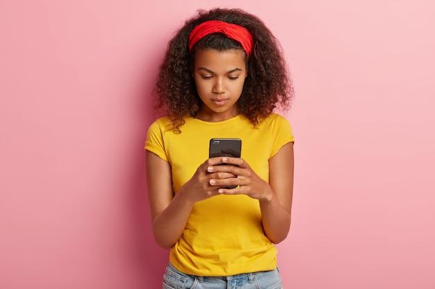 Zdjęcie uroczej nastolatki z kręconymi włosami pozowanie w żółtej koszulce