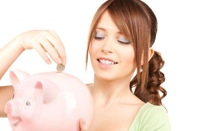 Zdjęcie uroczej nastolatki ze skarbonką i monetą