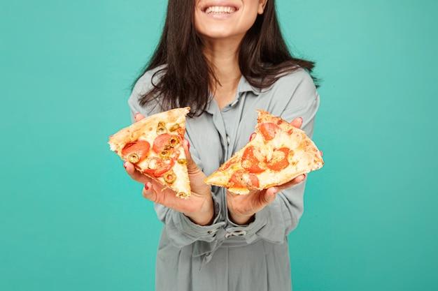 Zdjęcie uroczej pani pokazuje pizzę, ciesz się fast foodami